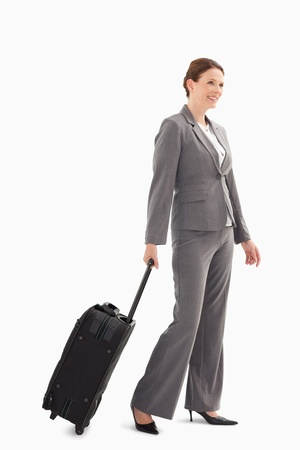 wheeling: A businesswoman wheeling a suitcase