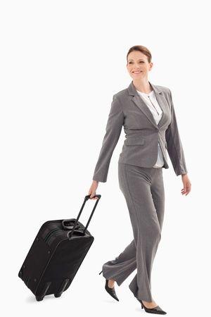 A businesswoman is smiling and walking with a suitcase photo