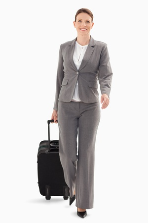 A businesswoman is walking forward with a suitcase photo