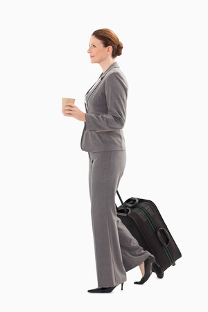 A businesswoman with a suitcase is holding coffee photo