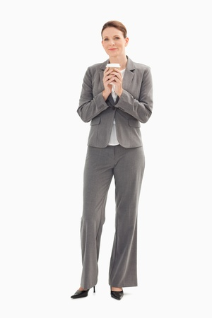 A businesswoman is holding a cup of coffee with her both hands photo