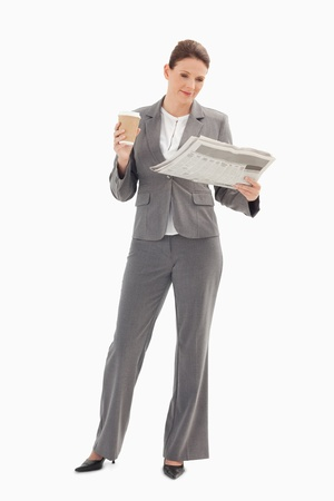 A businesswoman is reading the newspaper and holding a cup of coffee photo