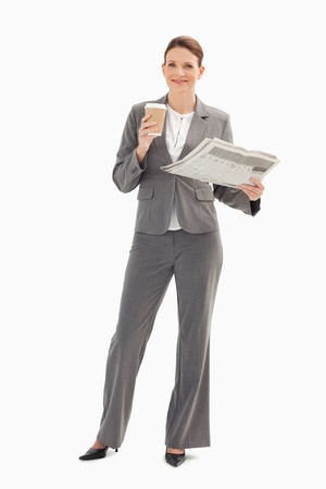 A smiling businesswoman is holding a cup and a newspaper Stock Photo - 13674526