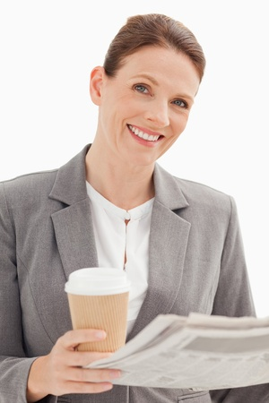 Smiling businesswoman holding newspaper and cup photo