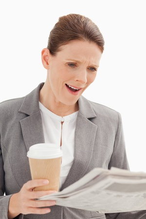 A surprised businesswoman is reading the newspaper photo