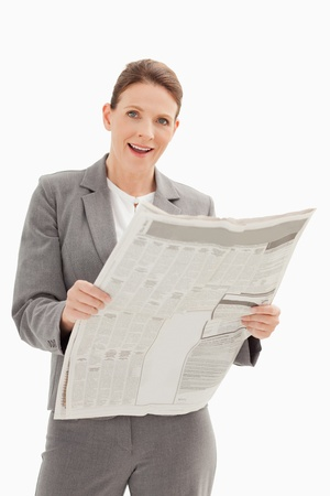 A surprised businesswoman is holding a newspaper photo