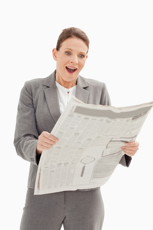 A surprised businesswoman is standing reading the newspaper photo