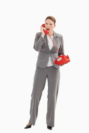 An angry businesswoman is talking on the phone photo
