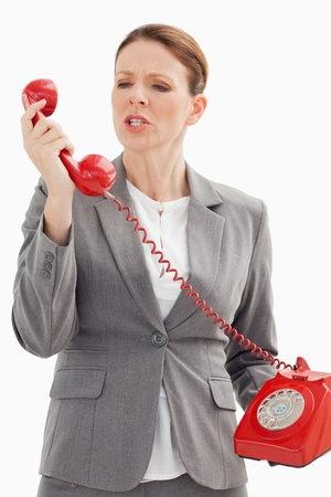 An angry businesswoman is shouting at the phone photo