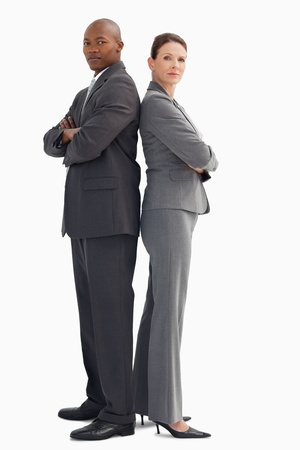 businessman standing: A business man and woman are standing with back to back
