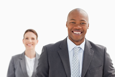 A smiling businesswoman stands behind smiling business man photo