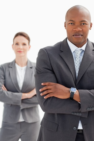 A businesswoman stands behind businessman photo