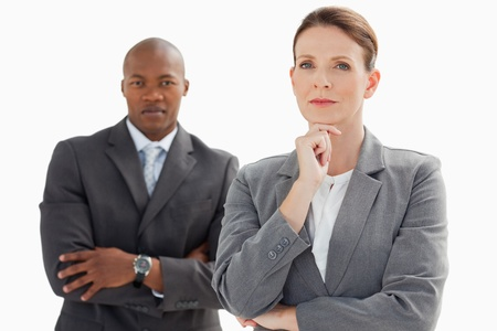 A businesswoman standing in front of businessman is resting her head on her hand  photo
