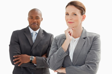 A smiling businessman stands behind businesswoman resting head on hand Stock Photo - 13671861