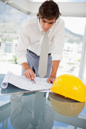 A businessman is looking at a construction drawings photo