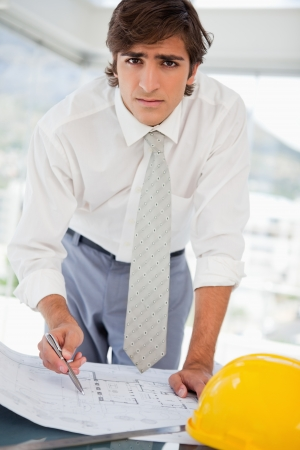 A businessman with a hard hat and construction drawings photo