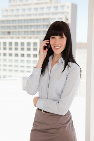 A woman in a sharp business suit at work making a call photo