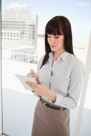 A woman looking at her note pad as she writes on it Stock Photo - 13672670