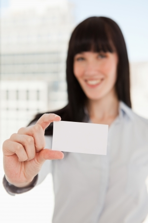 A focused shot on the business card as it is held by a business woman photo