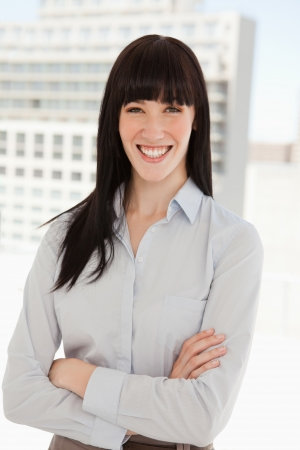 A woman smiling in her office and her arms folded photo