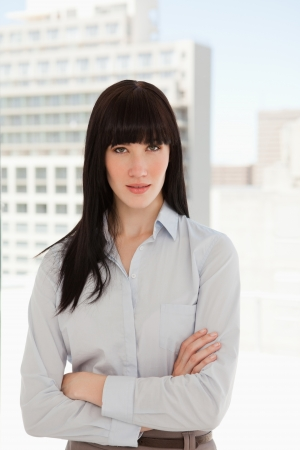 A business woman in her office with her arms crossed over photo