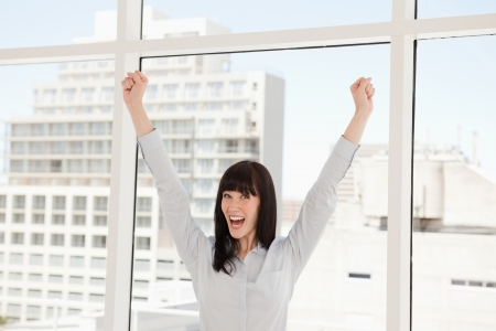 A celebrating business woman with her arms raised up in the air photo