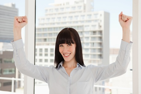 A happy business woman with her arms raised above her head in celebration photo