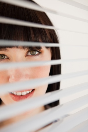 A woman smiling as she looks out through her unmoved  blinds on the window photo