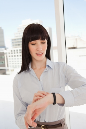 A business woman looking at her watch while in her office photo