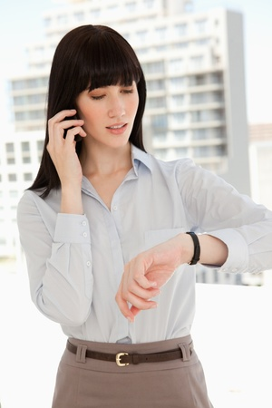 A woman checking the time as she makes a phone call photo
