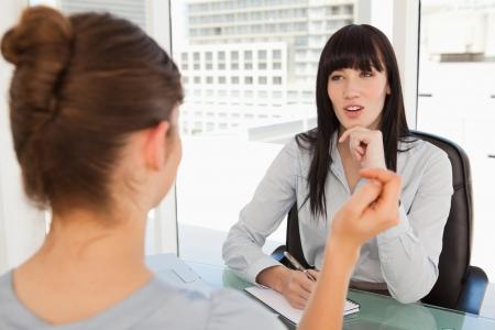 dos personas hablando: A las conversaciones de los empleados potenciales a la mujer de negocios en su oficina