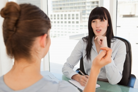 A potential employee talks to the business woman in her office photo