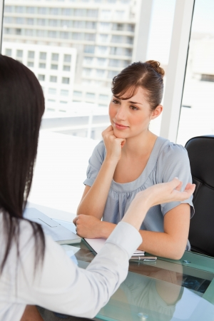 Brunette and black haired co workers chat to one another in an office photo
