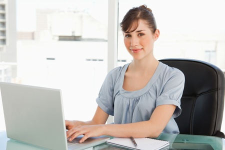 An attractive employee sits at her desk while typing on her laptop and looking into the camera Stock Photo - 13672560