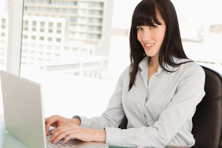 A smiling business woman looks into the camera as she types photo