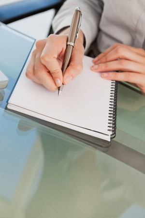 A close up shot of a woman taking down some notes on a notepad Stock Photo - 13670565