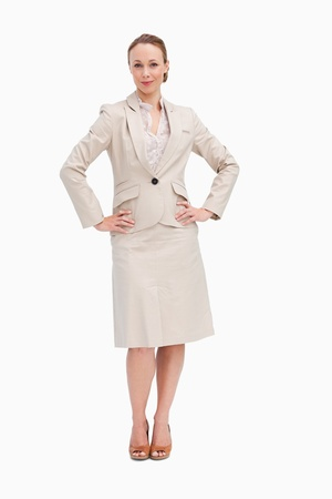 Portrait of a woman in a suit with her hands on her hips against white background photo