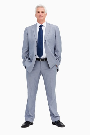 Portrait of a businessman with his hands in his pockets against white background photo
