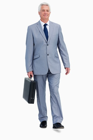 Portrait of a businessman with a suitcase walking against white babckground photo