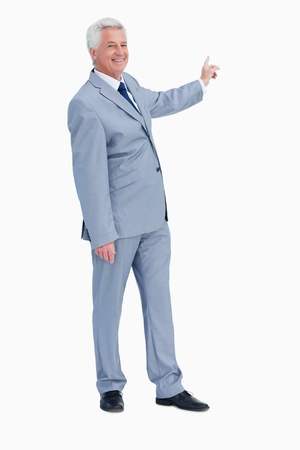 Portrait of a businessman pointing behind him against white background photo