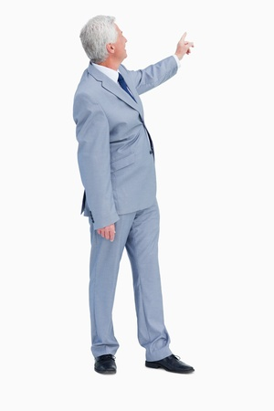 Businessman pointing behind him against white background photo