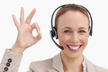 Woman in a suit with a headset approving against white background photo
