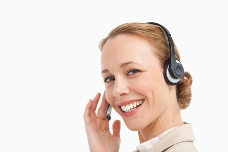 Portrait of a pretty woman in a suit with headset against white background photo
