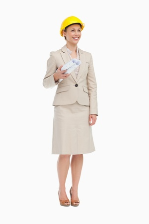 Woman in a suit wearing a safety helmet against white background photo