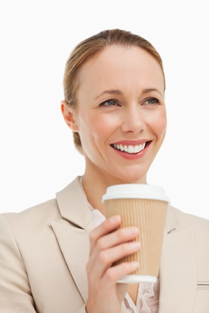 Woman in a suit holding a takeaway coffee against white background photo