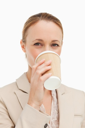Portrait of a woman in a suit drinking a takeaway coffee against white background photo