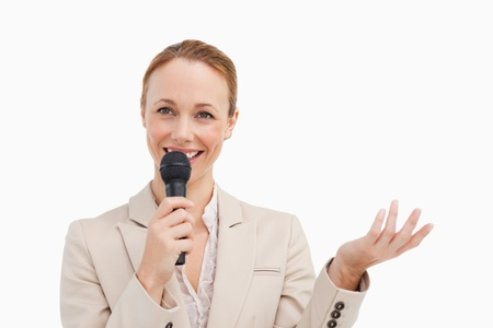 Pretty woman in a suit speaking with a microphone against white background photo