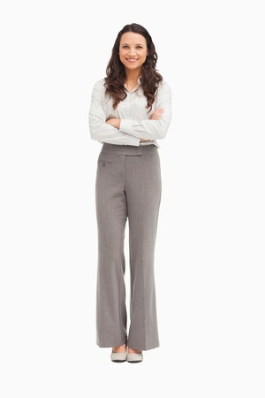 Pretty employee with folded arms against white background photo