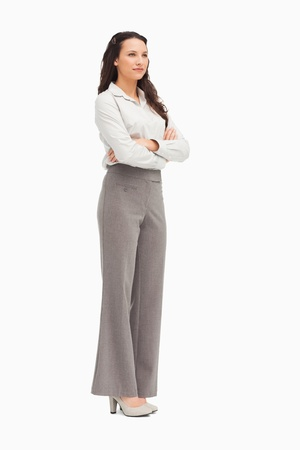 Cute employee with folded arms against white background