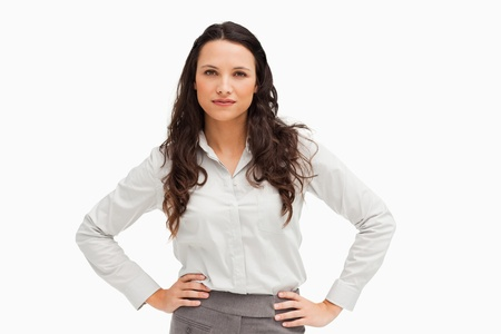Portrait of a brunette businesswoman hands on hips against a white background photo